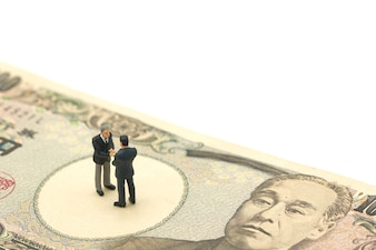 Miniature 2 people businessmen Shake hands Stand on Japanese banknotes