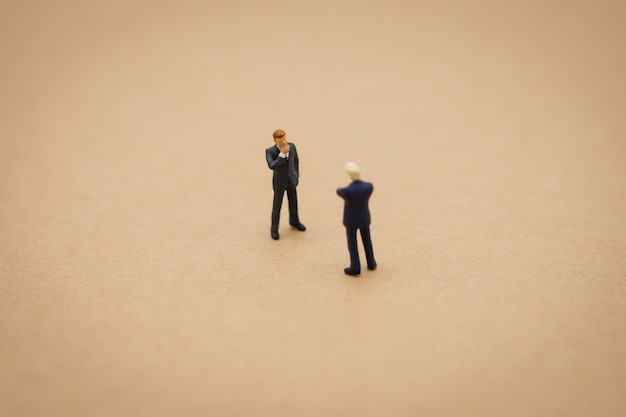 Miniature 2 people businessmen standing with back negotiating in business.
