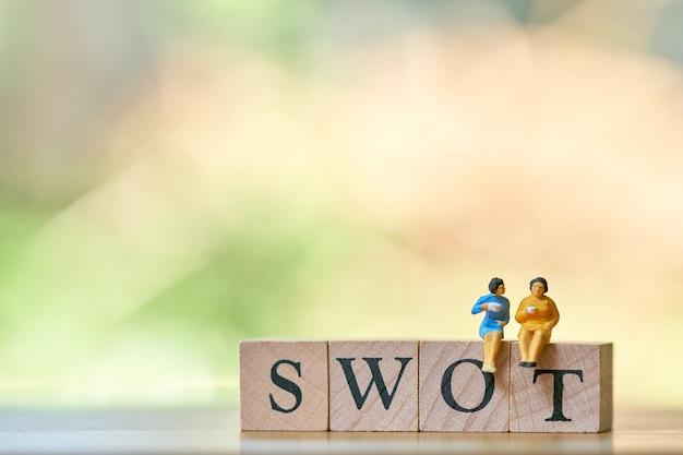 Miniature 2 people sitting on wood word swot