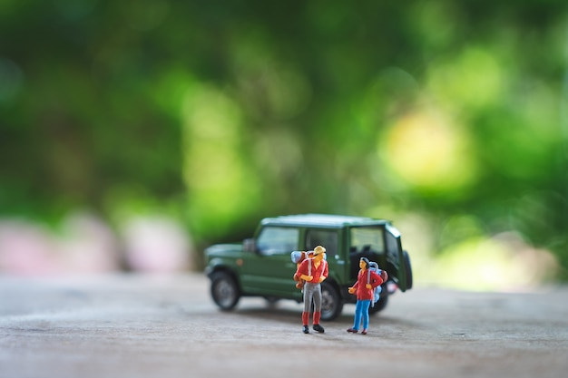 Miniature 2 people standing travel planner with yellow toy car model