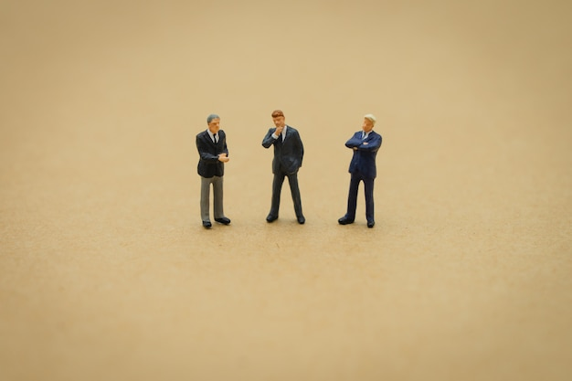 Miniature 3 people businessmen standing with back negotiating in business.