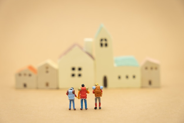 Miniature 3 people stand on house and hotel models to choose a place to live in.