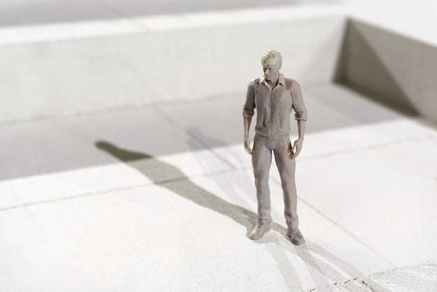 Miniature 3d printed monochrome figure of a man in leisurewear standing on tiles casting a shadow in the sunlight with copyspace