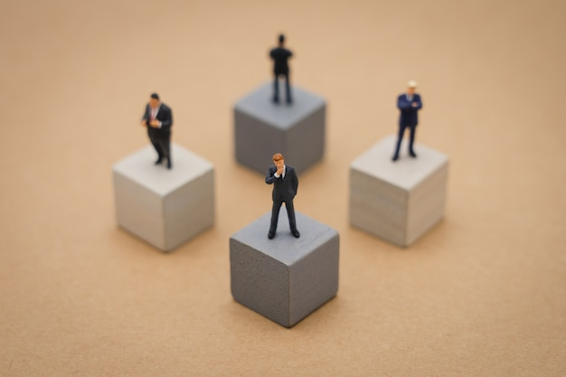 Miniature 4 people businessmen standing on wooden cube investment analysis