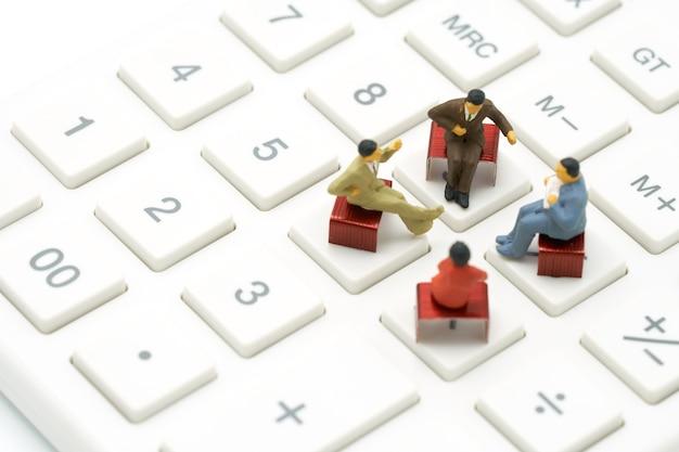 赤い針に座っているミニチュア4人が白い電卓に置かれています。