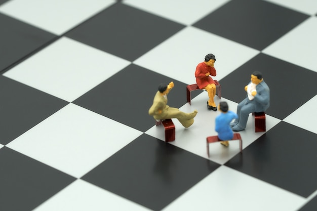 Miniature 4 people sitting on red staples placed on a a chessboard.