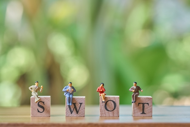 Miniature 4 people sitting on wood word swot