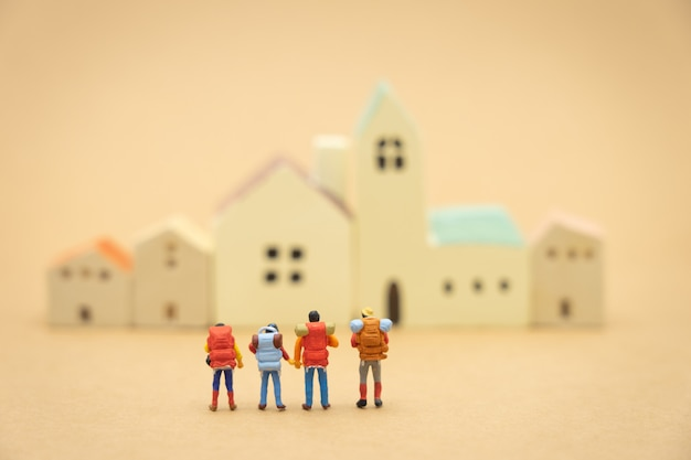 Miniature 4 people stand on house and hotel models to choose a place to live in.