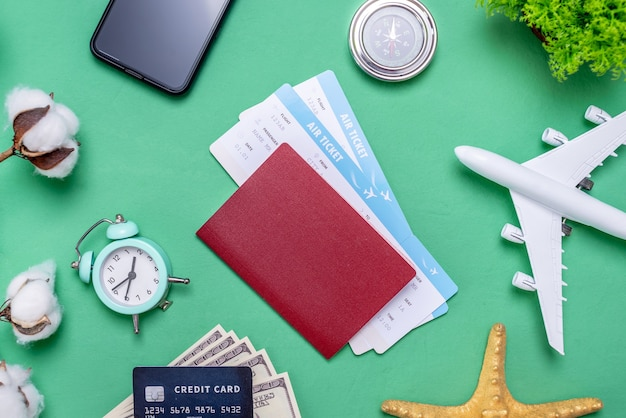 Miniature of an airplane, tickets and passport, and travel accessories on a green background