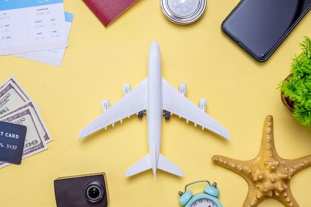 Miniature airplane and travel accessories on a yellow background