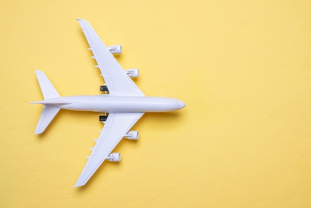 Miniature of an airplane on a yellow background with a copy space, top view