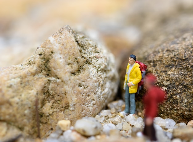 Miniature backpack travelers hiking rock, travel concept