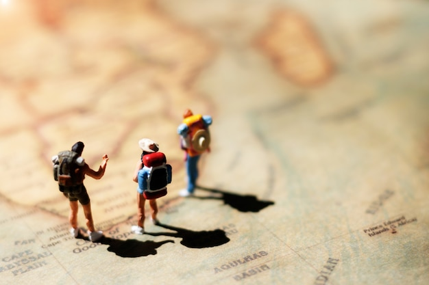 Miniature backpacker standing on world map.