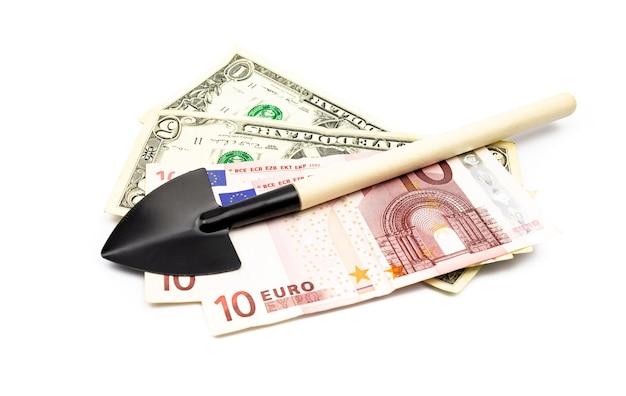 Miniature black spade with a wooden handle on a heap of banknotes close-up with isolate white background.