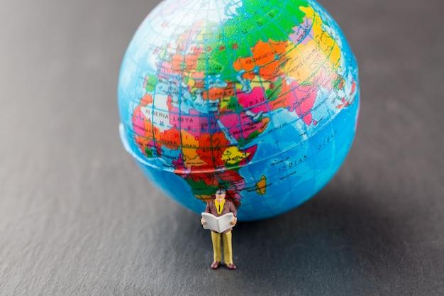 Miniature business man reading newspaper near world map model globe.