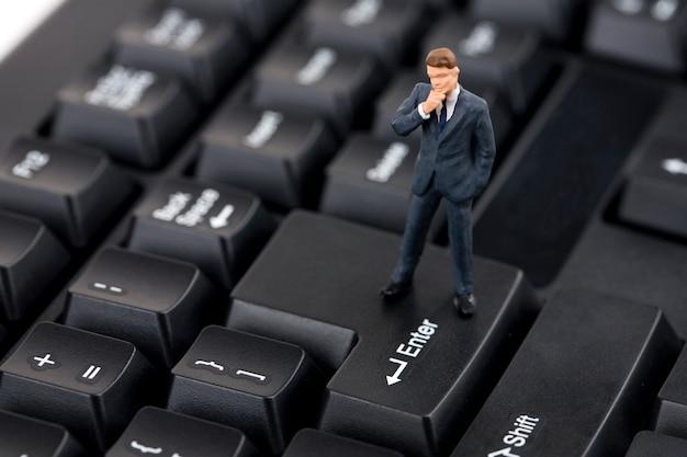 Miniature business man standing on a keyboard