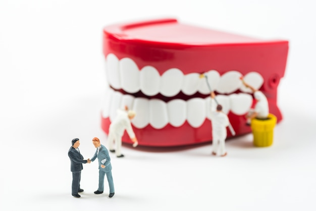 Miniature business people shaking hand to make agreement with teeth model background Premium Photo