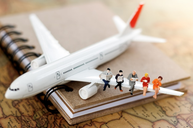 Miniature business people sitting on airplane with world map using as travel and business concept.
