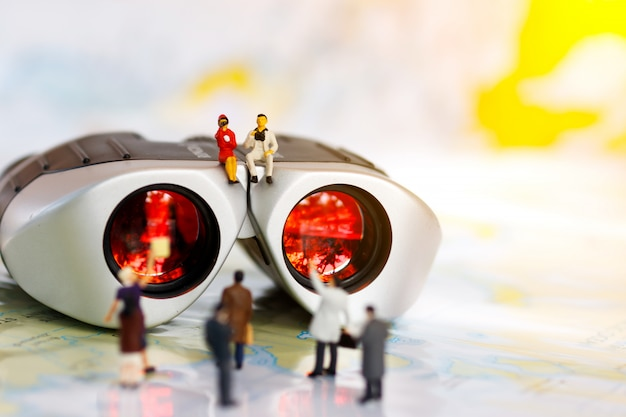 Miniature business people sitting on top of binoculars for finding people to work, recruitment concept.