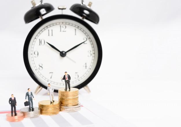 Миниатюрные деловые люди стоят на куче золотых монет с будильником на фоне, тайм-менеджмент сделал компанию успешной.