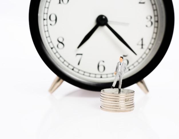 ミニチュアビジネスの人々は目覚まし時計の背景を持つ銀のコインの上に立つ、時はお金の概念