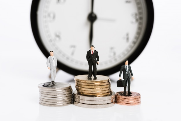 Miniature business people stand on silver coins with alarm clock background, time is money concept