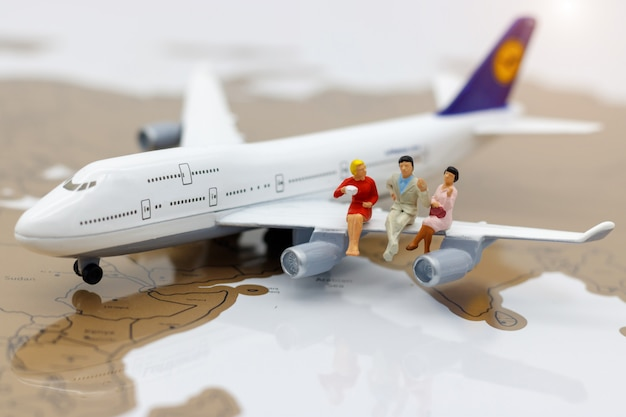 Miniature business people with sitting on airplane.