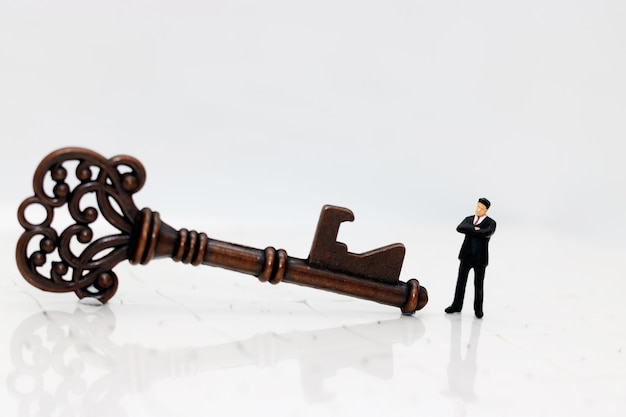 Miniature business people with the success key