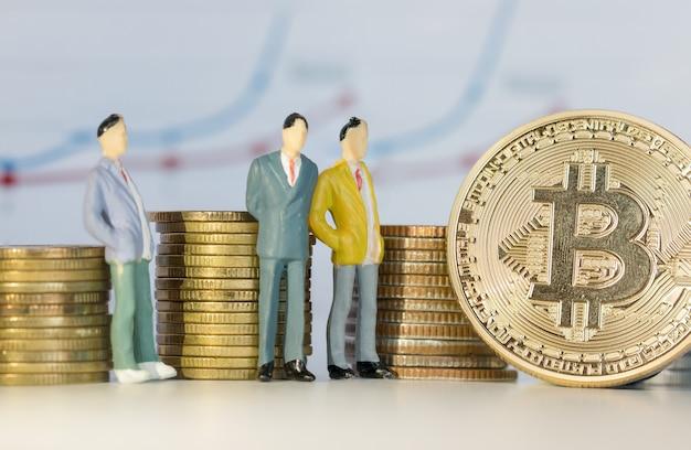 Miniature business standing near bitcoin digital virtual money on stack coins