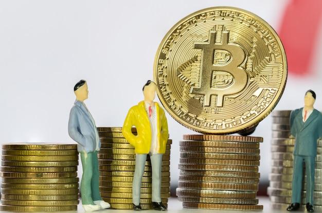 Miniature business standing near bitcoin digital virtual money