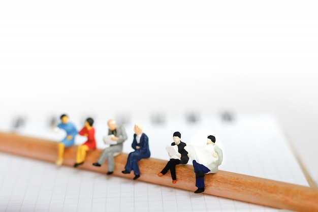 Miniature business team sitting on pencil and book.