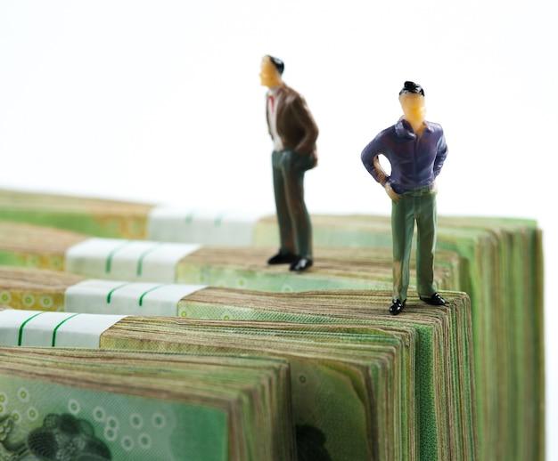 Miniature businessman on banknotes