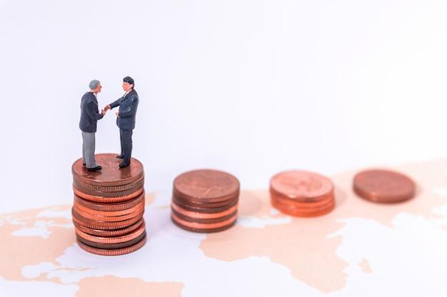 Miniature businessman handshake on world map. on white