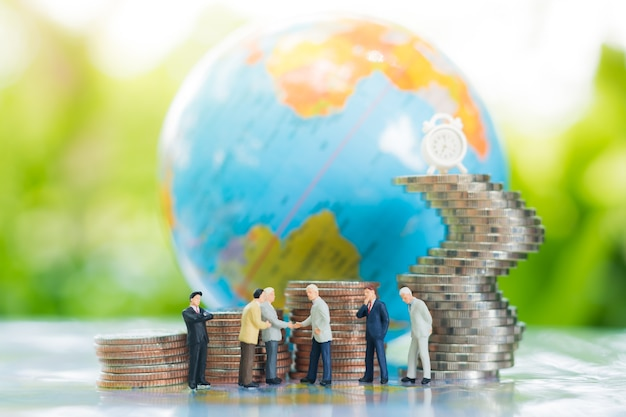 Miniature businessman handshaking with globe and growing stacks of coins background.