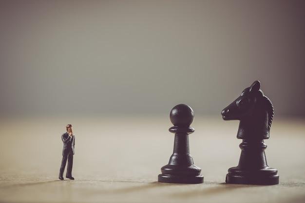 Миниатюрный бизнесмен перед шахматными фигурами. бизнес-концепция.
