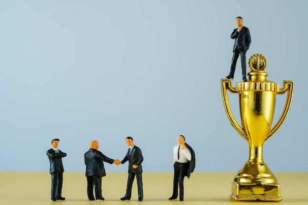 Миниатюрный бизнесмен на золотых трофеях и рукопожатии бизнесменов.