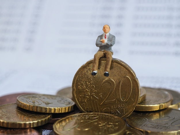 Miniature businessman sit on euro coins and book bank. business and idea concept.