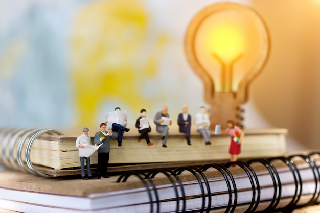 Miniature businessman sitting on book with lamp.