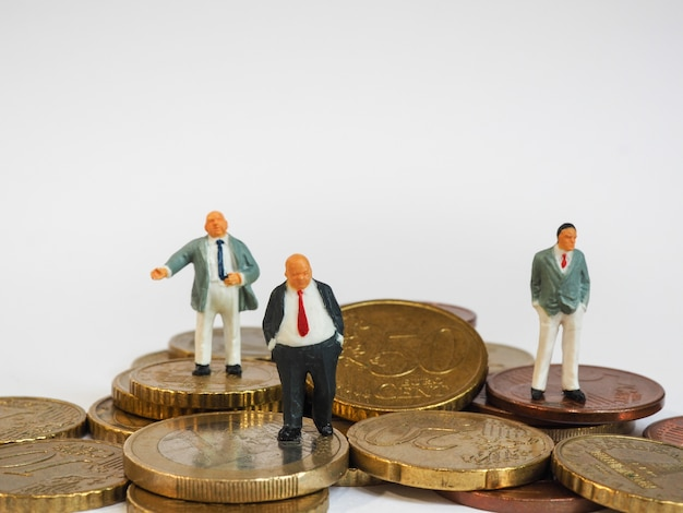 Miniature businessman stand on euro coins and book bank. business and idea concept.