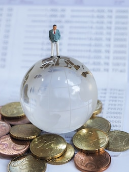 Miniature businessman stand on globe of glass, euro coins and book bank.