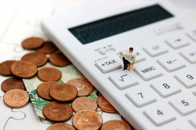 Miniature businessman stand reading on tax button of calculator.