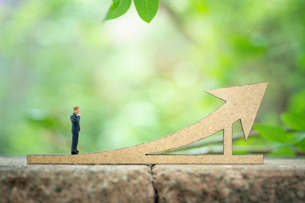 Miniature businessman standing on graph for environmentally friendly