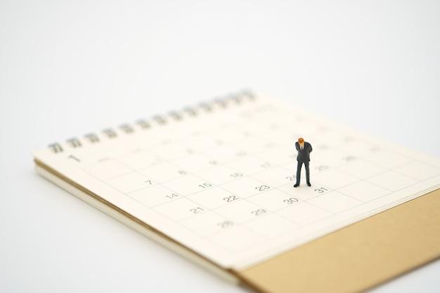 Miniature businessman standing on white calendar