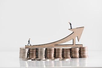miniature businessman walking on uptrend financial graph