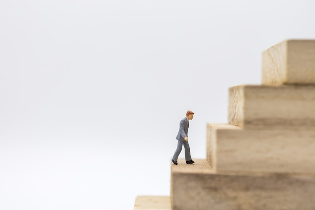 Miniature of businessman walking to top of stack of wooden block toy