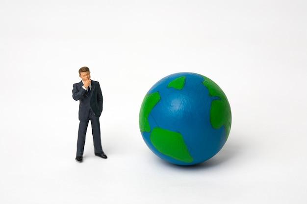 Miniature businessman with globe on white