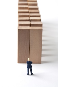 Miniature businessman with multiple obstacle walls