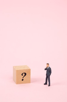 Miniature businessman with question mark on wood cube