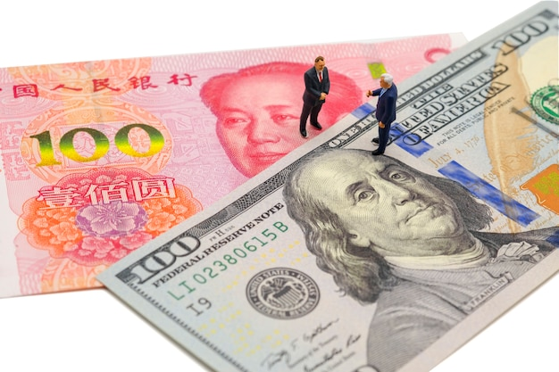 Miniature businessman with us dollar and china yuan banknote on corporate meeting
