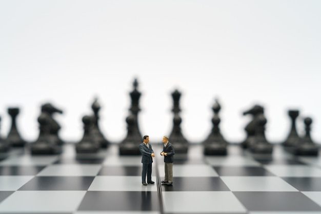 Miniature businessmen 2 people standing on a chessboard with a chess piece